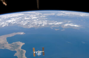 With the International Space Station in the foreground, this photo was taken from the Space Shuttle as it left the ISS (notice the Shuttle's tail in the top middle).  Where is this?  To the left is the boot of Italy, with the blue Mediterranean and Greece beyond.  Note the clouds forming as the land heats up and the air rises.                                                  Courtesy Dan Barstow
