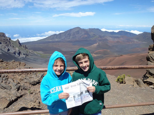 "Chris and Jen Rodstrom brought along The Stow Independent on their family vacation to Los Angeles and Hawaii. Pictured are kids Sarah and Mark Rodstrom on the rim of the crater at the to the top of the Haleakala volcano on Maui, 10,000 feet above the Pacific Ocean visible beyond the clouds in the background. This was the real ""high point"" of our vacation, which also included a visit to Oahu and a flight home just before the first of the twin tropical storms arrived in Hawaii."
