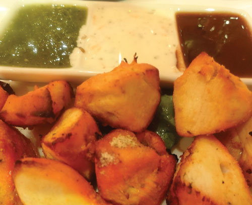 The chicken tikka starter is served with a sauce trio of tangy tamarind, cool raita, and cilantro-mint chutney.