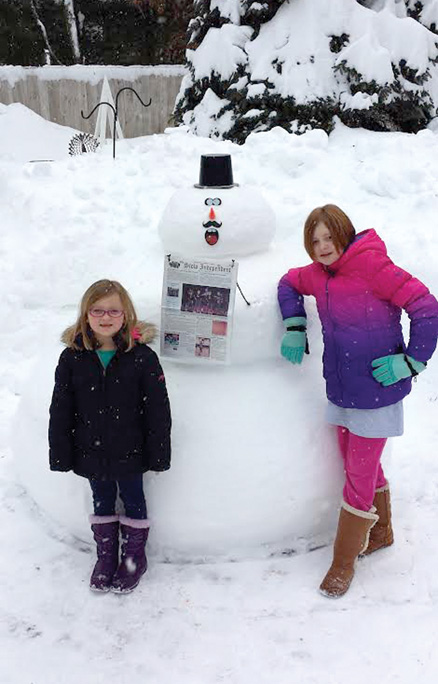 Samantha & Avery Kerr standing next to their snowman made with help from their grandfather.