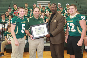Coach Tucker receives his award from former New England Patriot Andre Tippett, with Nashoba Football Co-Captains Jake Benjamin #5  and  Mike Curtin #52.             Courtesy