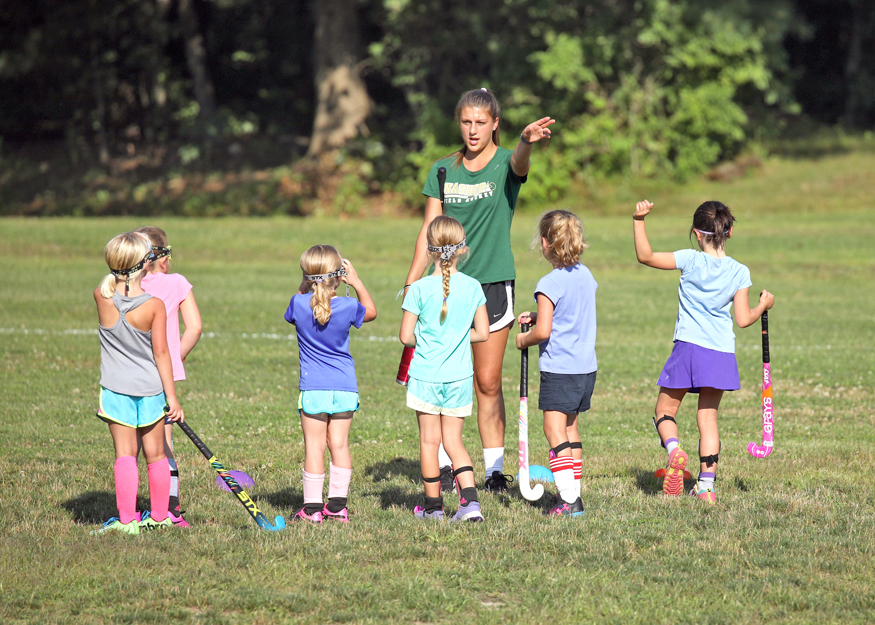 Nashoba High Field Hockey team member Erin Mehigan from Stow assists young players at an Aug. 9 skills clinic sponsored by Nashoba Youth Field Hockey SusanShaye.com